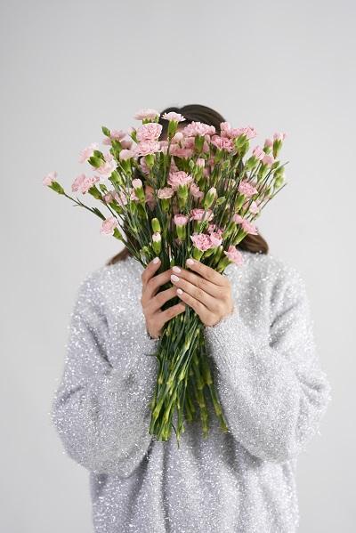 Mujer escondida detrás de un ramo de flores
